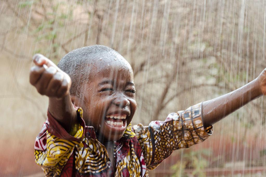Child in the rain, by Riccardo Mayer, Shutterstock, Travel Africa magazine
